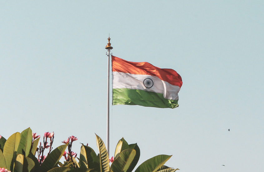 India flag against blue sky and some plants