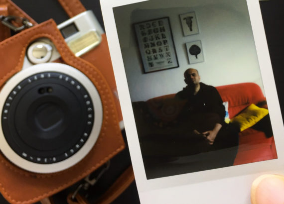 hand holding polaroid picture with camera in background